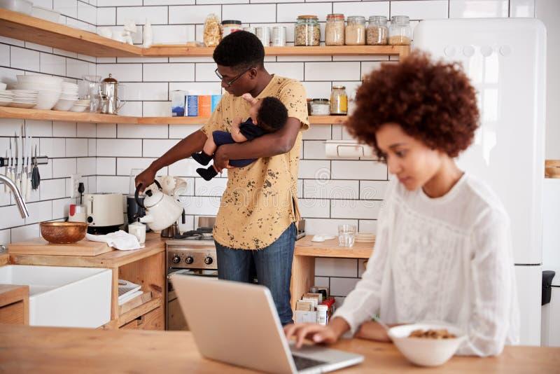Le père multitâche Holds Baby Son et verse la boisson pendant que la mère utilise l'ordinateur portable et mange le petit déjeune photo stock