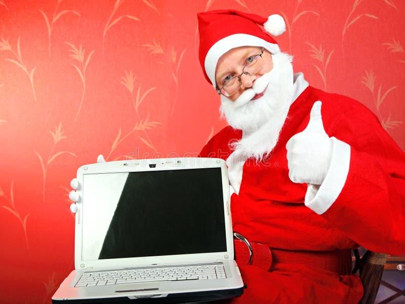 Le père noël avec l'ordinateur portatif photo stock