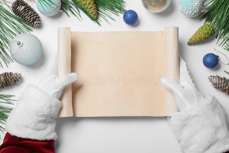 Le Père Noël avec son parchemin vierge et son décor de Noël en arrière-plan, vue de haut Espace pour le texte images stock