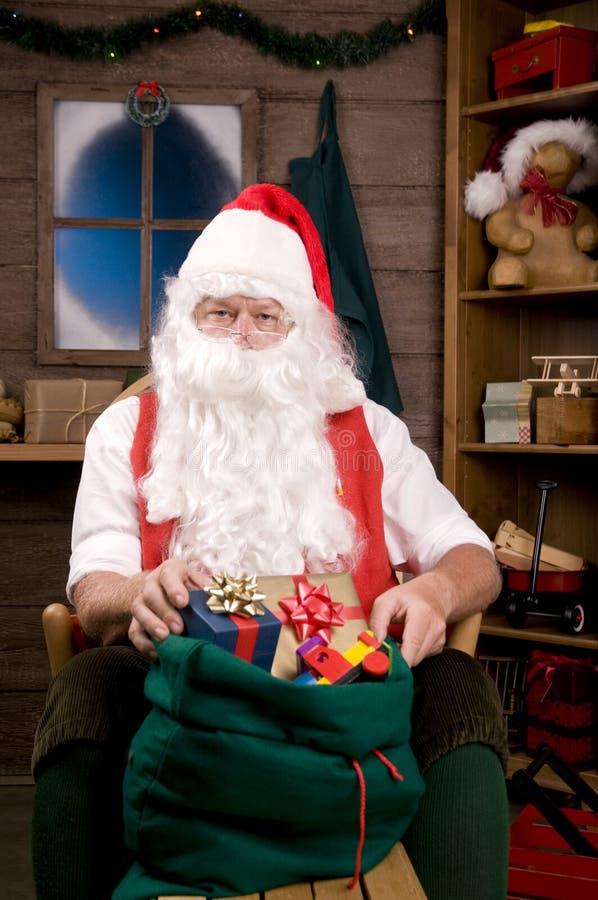 Le père noël dans l'atelier avec le sac des jouets photographie stock libre de droits