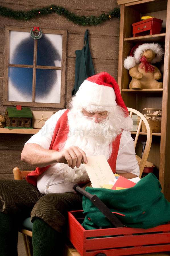 Le père noël dans l'atelier avec le sac des lettres photo libre de droits