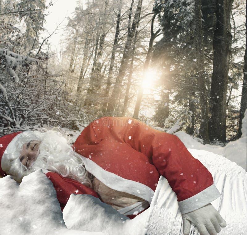 Le père noël dormant dans l'environnement de forêt couvert de neige images libres de droits