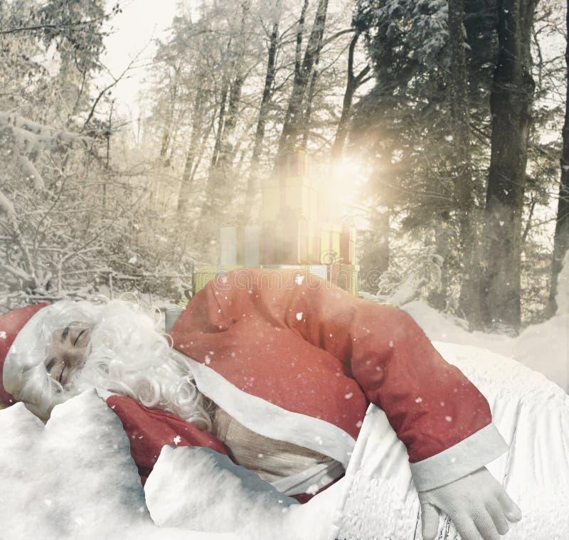 Le père noël dormant sur la neige devant des cadeaux à la forêt entourent image stock