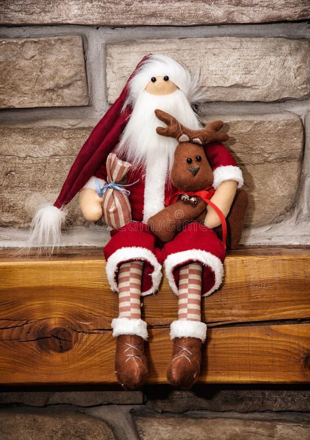 Le père noël a fait du tissu se repose avec le renne au-dessus du ston photographie stock