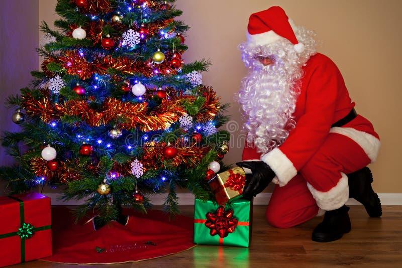 Le père noël fournissant des présents sous l'arbre. photos libres de droits