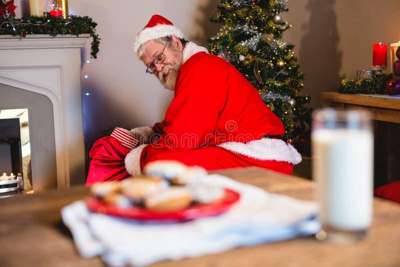 Le père noël mettant des présents dans le sac de Noël photo libre de droits