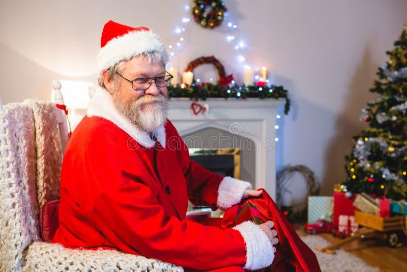 Le père noël mettant des présents dans le sac de Noël photo stock