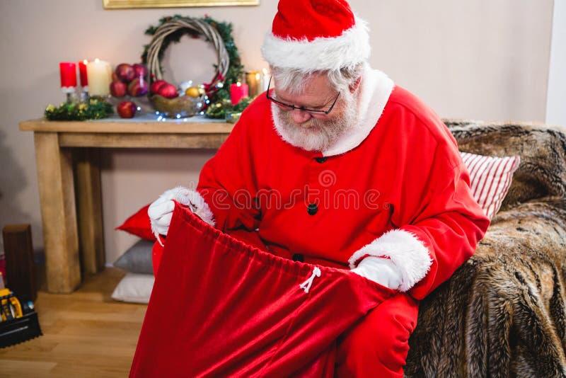 Le père noël regardant dans son sac à cadeau photo stock