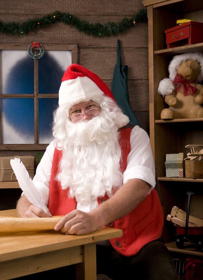 Le père noël s'asseyant dans son atelier avec le crayon lecteur de cannette photo stock