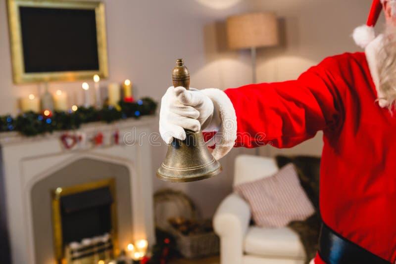 Le père noël sonnant une cloche à la maison pendant le temps de Noël photographie stock libre de droits
