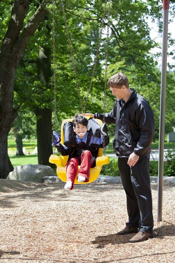 Le père poussant le garçon handicapé dans les besoins spéciaux balancent image stock