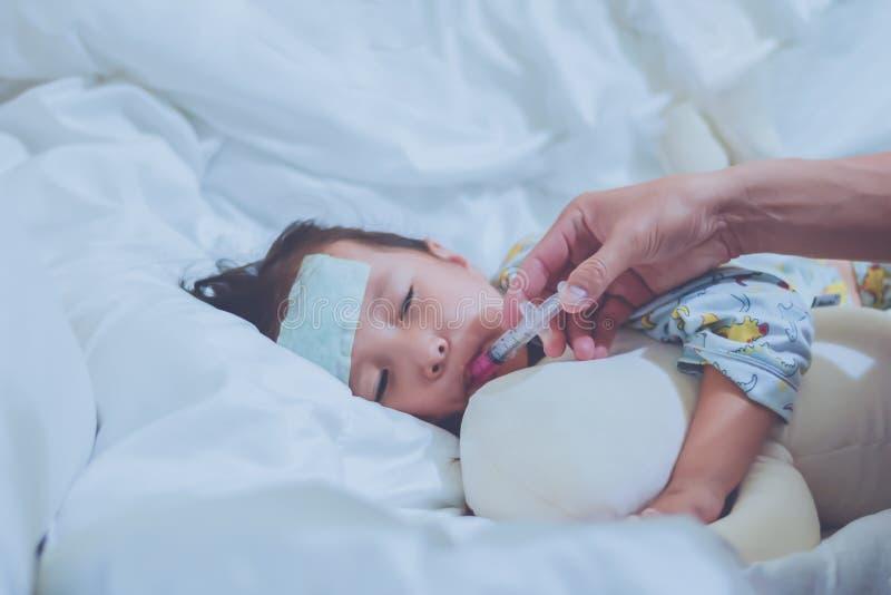 Le père prend la médecine antipyrétique à la petite fille malade dans la chambre à coucher à la nuit avec la seringue, enfant a d photos libres de droits