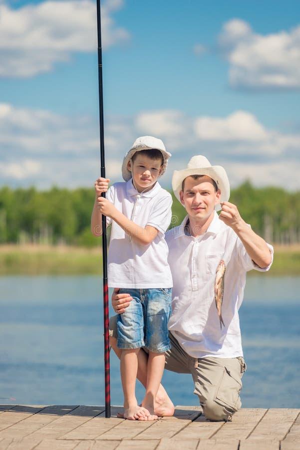 Le père prouve aux poissons que son fils a attrapé photos libres de droits
