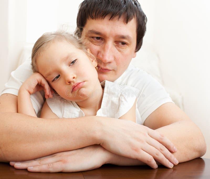 Le père soulage une fille triste photo stock