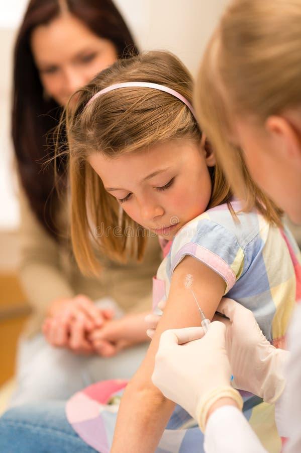Le pédiatre de vaccination d'enfant appliquent l'injection photo libre de droits