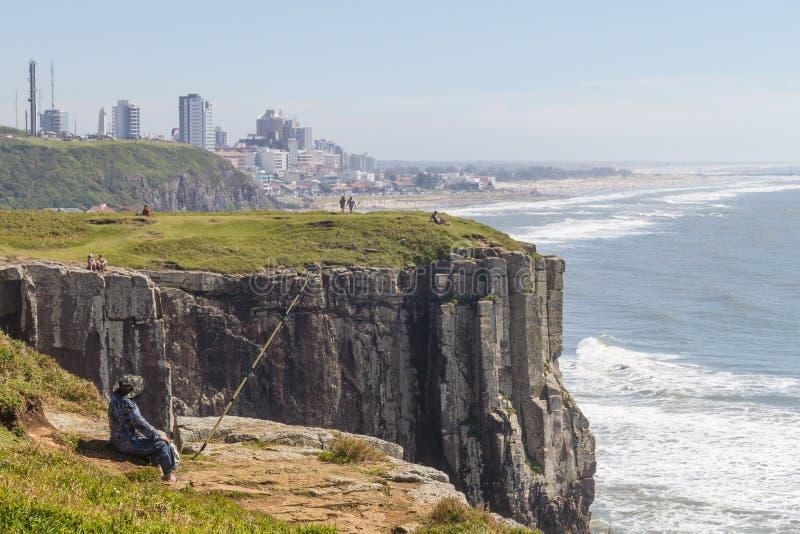 Le pêcheur au-dessus des falaises et les vagues chez Torres échouent image stock