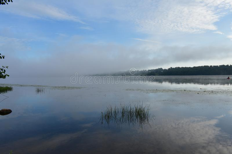 Le pêcheur de rivière de matin sur un bateau, des nuages de ciel bleu s'est reflété dans le lisse photographie stock libre de droits