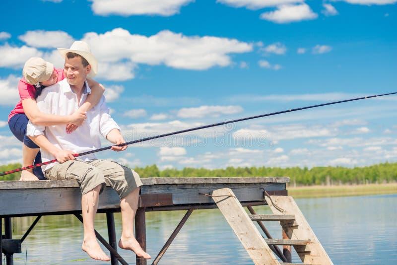 Le pêcheur et son épouse sur un pilier en bois près du lac, un homme est images libres de droits