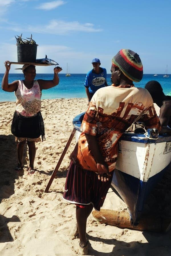 le pêcheur local débarquant le sien crochet et discute des événements actuels tandis qu'un de la dame du marché prend le transpor photographie stock libre de droits