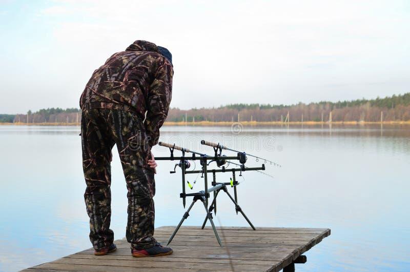 Le pêcheur observe des conducteurs sur la cosse de tige avec les alarmes électroniques de morsure photo libre de droits