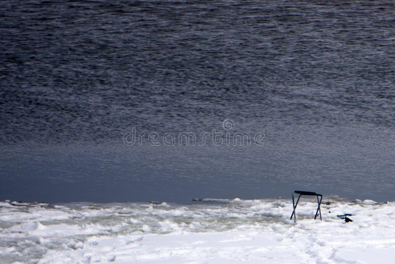 Le pêcheur regarde avec cette présence de caméscope des poissons sous la glace images libres de droits