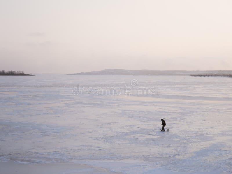 Le pêcheur s'assied près du trou de glace sur la rivière congelée au coucher du soleil photo libre de droits