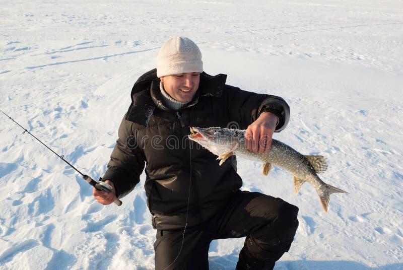 Le pêcheur sur la pêche de l'hiver photo libre de droits
