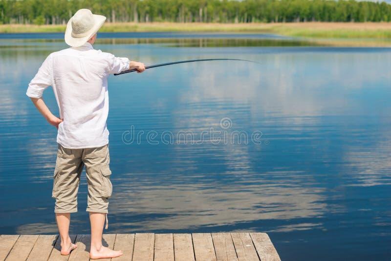 Le pêcheur sur le pilier avec une canne à pêche pêche les poissons, le v photographie stock libre de droits