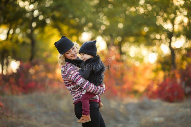 Le p?re et le b?b? heureux de m?re de famille l'automne marchent en parc photographie stock libre de droits