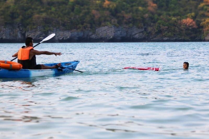 Le p?re et la fille asiatiques sont enseignants et formants la garde ou la d?livrance de vie sur la plage image stock