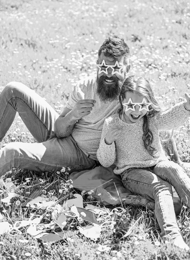 Le p?re et la fille s'assied sur l'herbe au grassplot, fond vert Enfant et papa posant avec la photo en forme d'?toile d'eyeglase images libres de droits