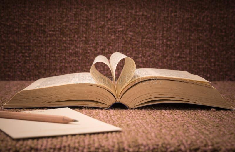 Le pagine del libro aperto hanno arrivato a fiumi la forma del cuore sulla tavola fotografia stock