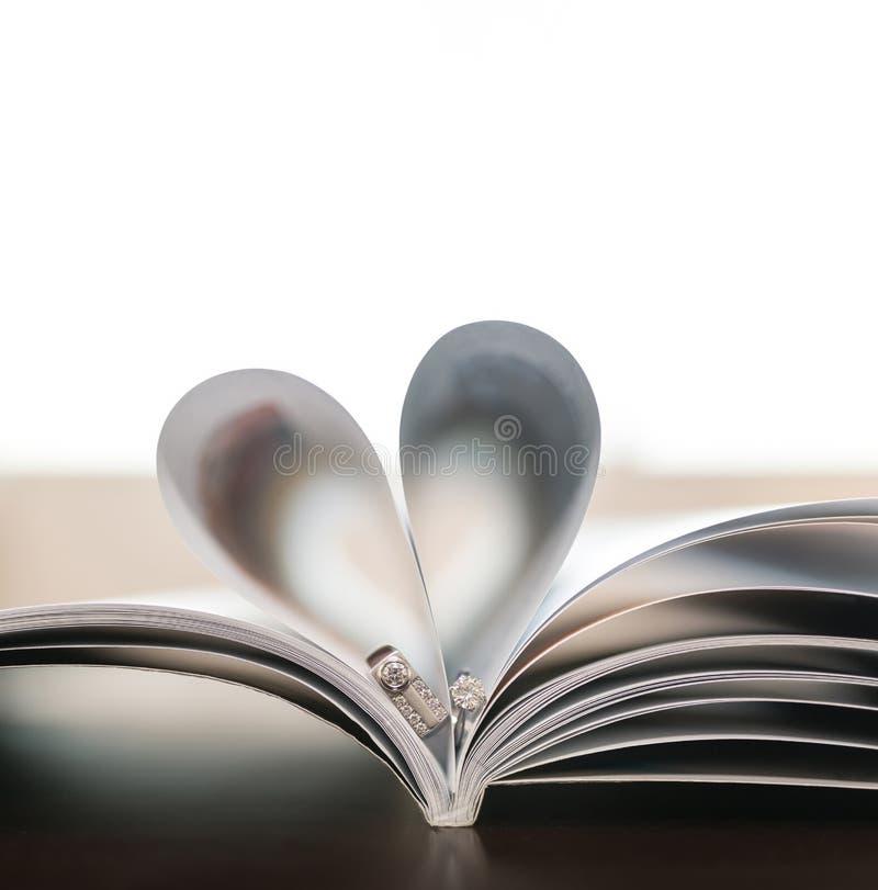 Le pagine del libro hanno curvato in forma del cuore con le fedi nuziali delle coppie fotografia stock libera da diritti