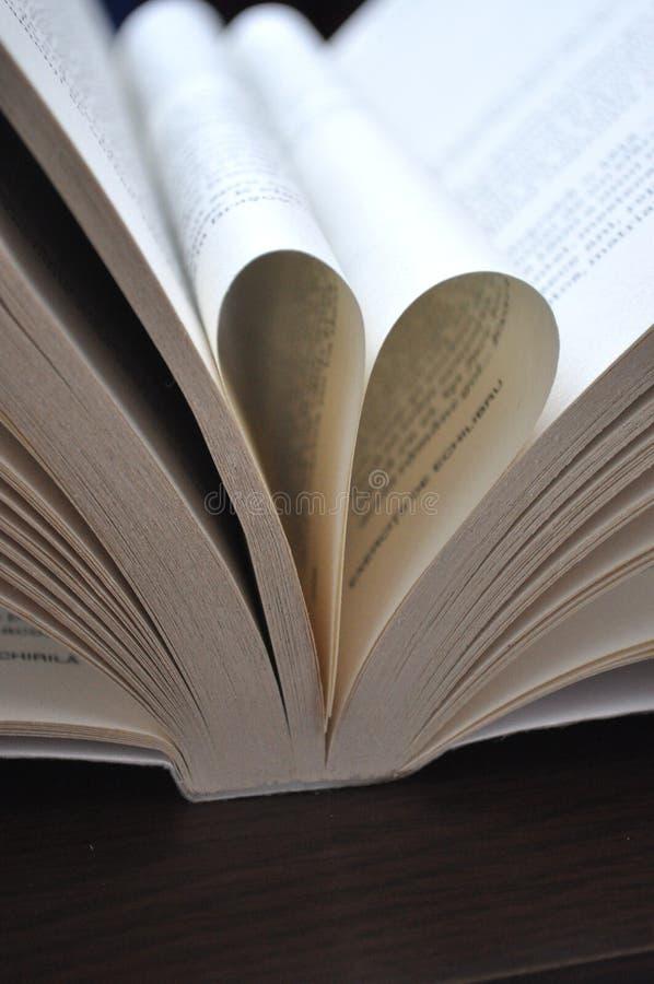 Le pagine del primo piano di un libro aperto, con cuore hanno modellato le pagine immagine stock