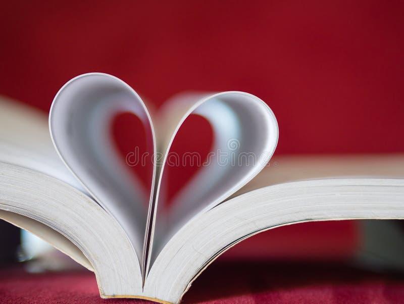 Le pagine molli del fuoco del primo piano di un libro hanno curvato in una forma del cuore immagine stock