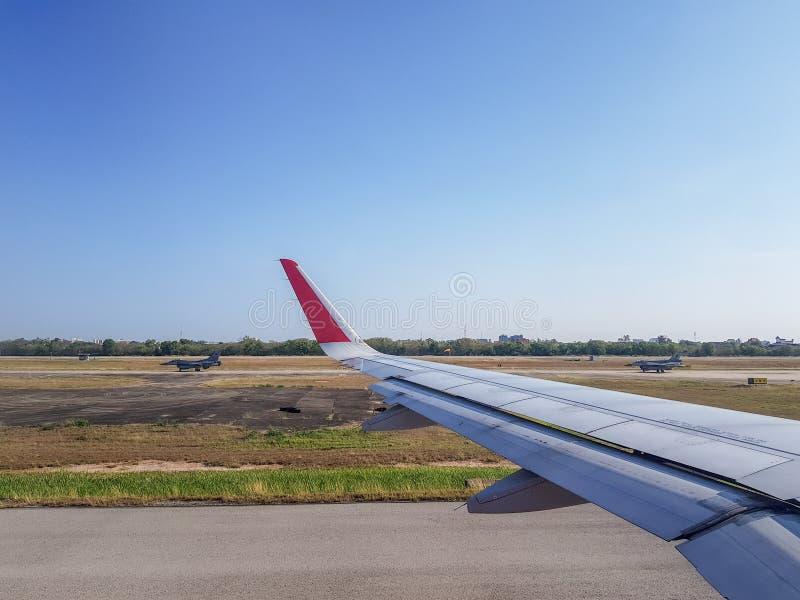 Le paia del funzionamento degli aerei da caccia dell'aeronautica passano l'aeroplano commerciale nell'aerodromo fotografie stock libere da diritti
