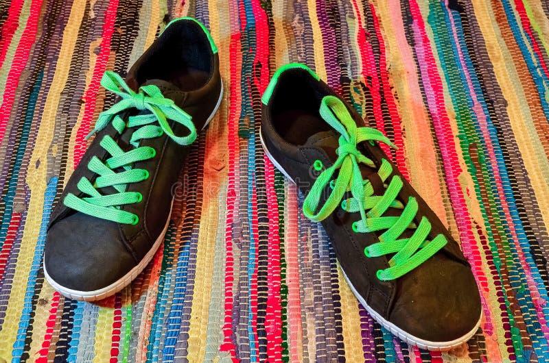 Le paia delle scarpe da tennis variopinte hanno messo sui precedenti del pavimento del textil fotografia stock