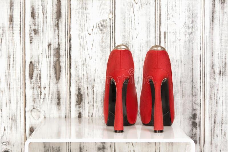 Le paia di bello color scarlatto degli alti sandali sexy rossi su un fondo di legno bianco immagini stock