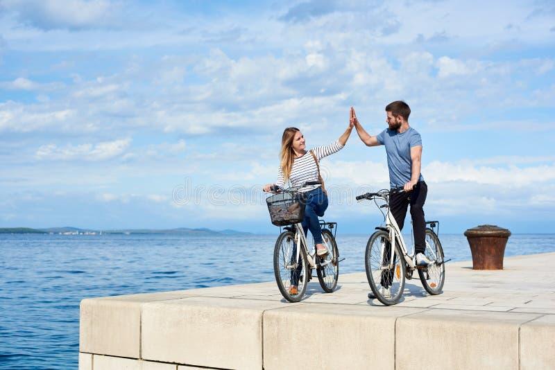 Le paia turistiche, l'uomo e la donna con le biciclette sul livello hanno pavimentato il marciapiede di pietra vicino all'acqua d immagini stock