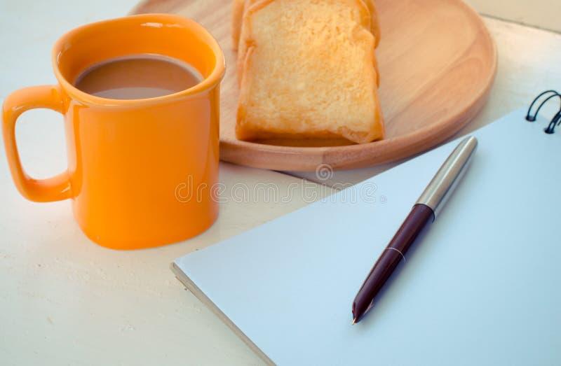 Le pain, café, le carnet, crayon sur le concept de bureau font une pause - la vie toujours photo libre de droits