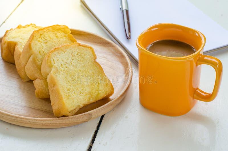 Le pain, café, le carnet, crayon sur le concept de bureau font une pause - la vie toujours photo stock