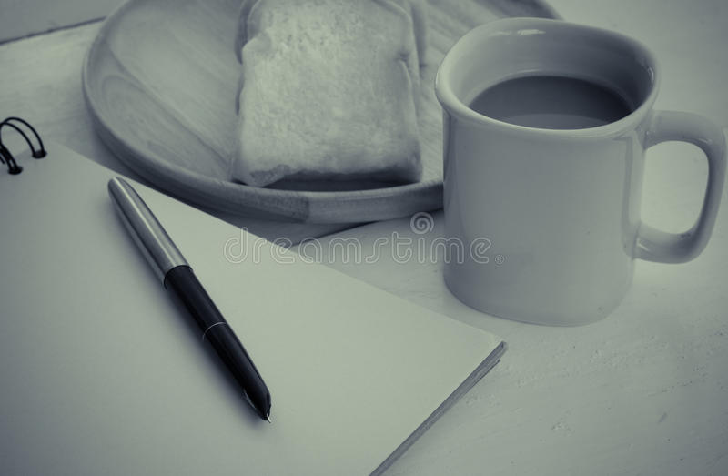 Le pain, café, le carnet, crayon sur le concept de bureau font une pause - la vie toujours image stock