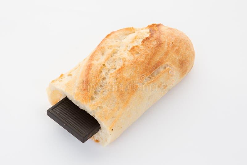 Le pain de baguette a coupé avec un morceau de chocolat dans lui image libre de droits