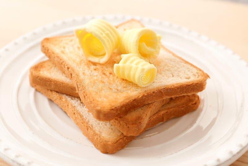 Le pain grillé avec du beurre se courbe du plat image libre de droits