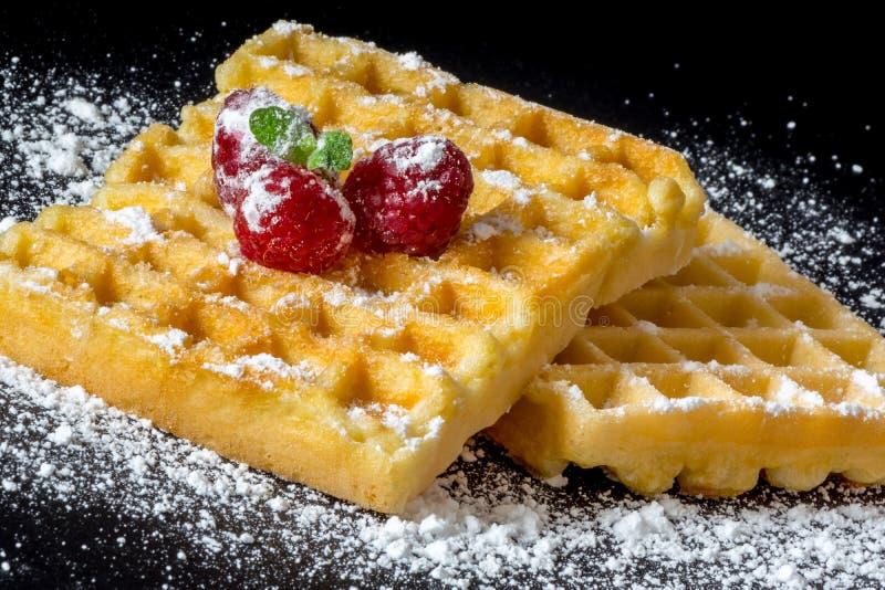 Le pain grillé doux waffles avec des framboises et un brin des feuilles en bon état et du macro en gros plan de poudre de sucre s photo stock