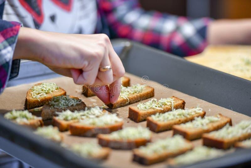 Le pain noir avec du fromage et des assaisonnements, la fille arrose le pain coupé en tranches image stock