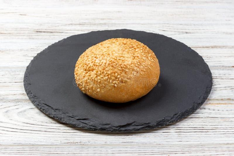 Le pain ou le petit pain cuit au four frais avec des graines de sésame et de tournesol sur l'ardoise embarquent image stock