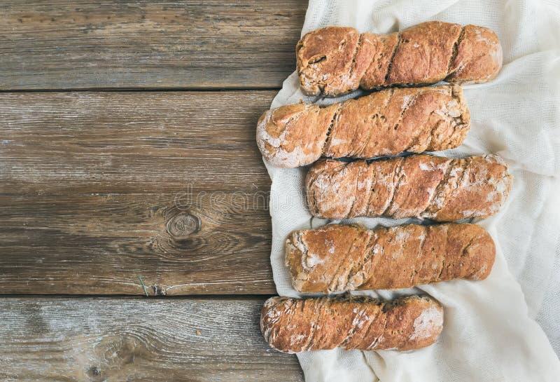 Le pain rustique fraîchement cuit au four de village (baguettes) a placé sur rugueux courtisent photos stock