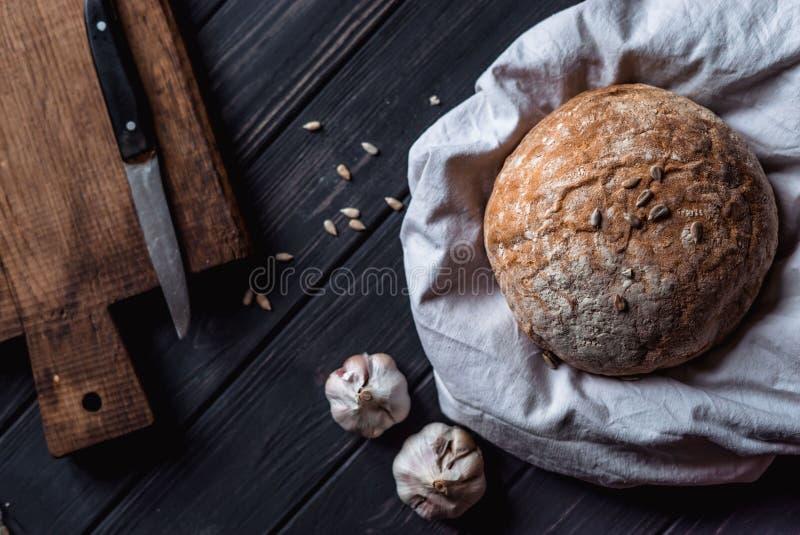 Le pain se trouve sur un tissu blanc sur une table en bois image stock