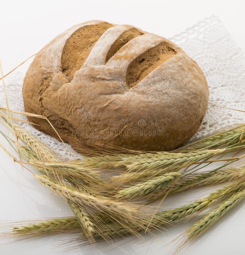 Le pain sur une table avec du blé se trouve sur une serviette de dentelle photos stock
